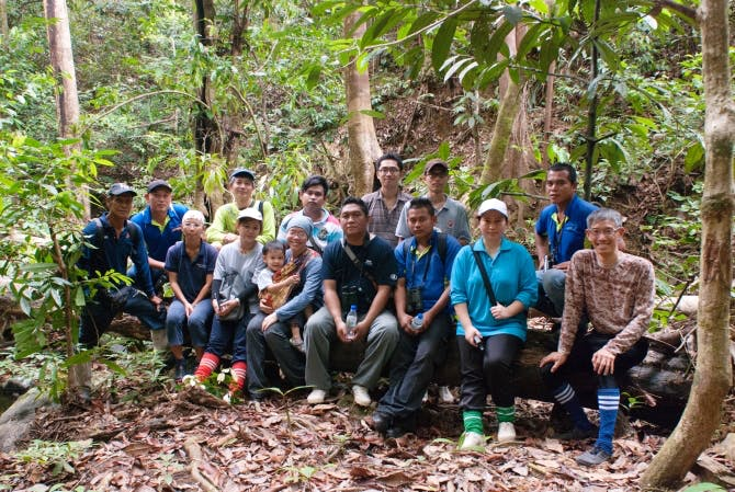 Team shot, MGumal, backrow, green top and blue cap, at field site, March 2014